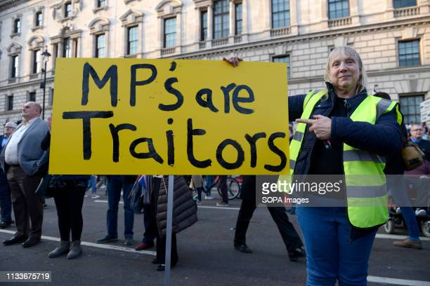 A pro Brexit protester seen holding an United Kingdom flag and a banner that says MP's are traitors during the Leave means leave rally in London A...