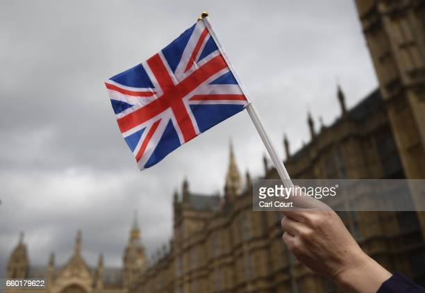 Pro Brexit supporter holds a Union Jack flag during a small pro EU demonstration near Parliament on March 29 2017 in London England Today British...