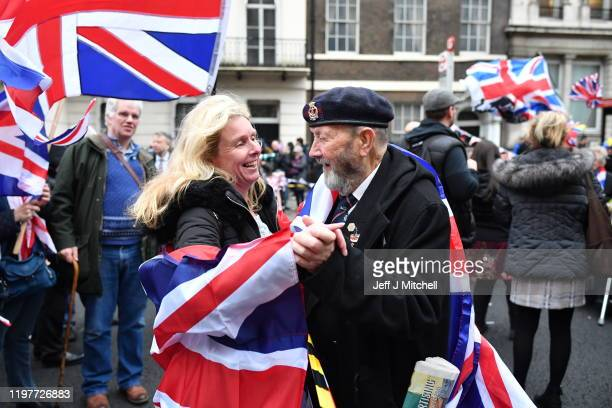 Pro Brexit supporters dance in the street draped with Union Jack flags at Parliament Square as people prepare for Brexit on January 31, 2020 in...