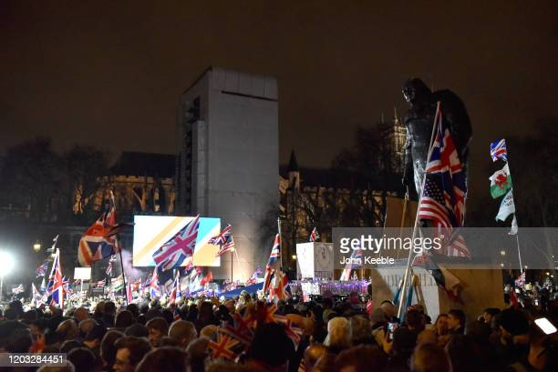 Pro Brexit supporters wave flags around the Winston Churchill statue during the Leave Means Leave Brexit day celebration party outside the Houses of...