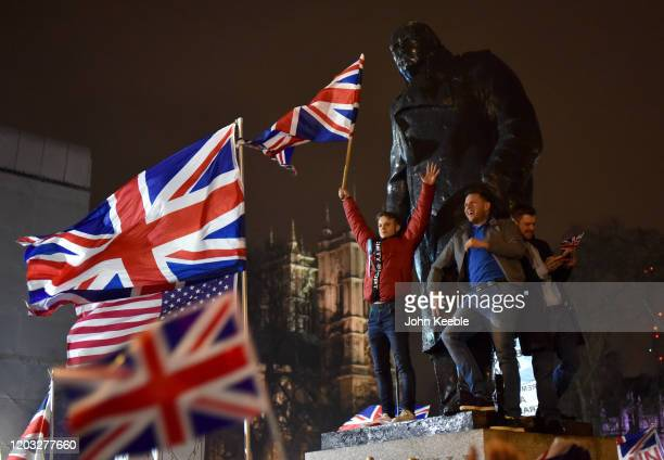 Pro Brexit supporters wave flags as they stand on the Winston Churchill statue during the Leave Means Leave Brexit day celebration party outside the...