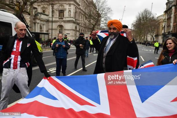Pro Brexit supporters wave Union Jack flags at Parliament Square as people prepare for Brexit on January 31, 2020 in London, United Kingdom. At...