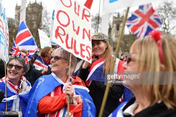 Pro Brexit supporters wave Union Jack flags while standing on a European Union flag at Parliament Square as people prepare for Brexit on January 31,...
