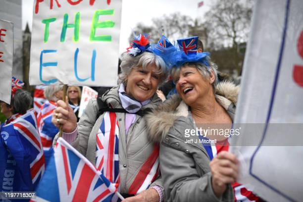 Pro Brexit supporters wear novelty Union Jack top hats outside the Houses of Parliament as people prepare for Brexit on January 31 2020 in London...