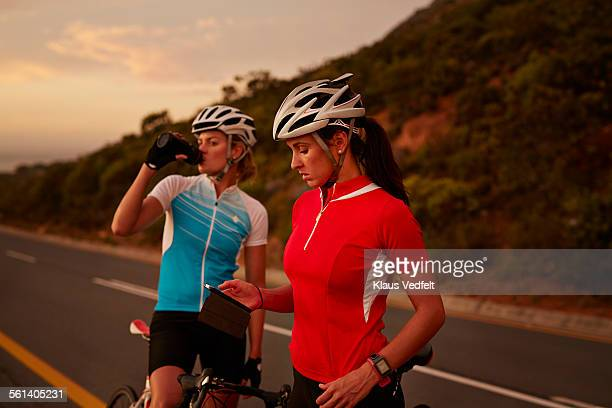 Pro cyclists checking phone & drinking water