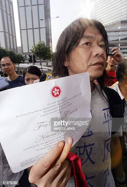 Pro democracy legislator Leung Kwok Hung shows his invitaion card to a cocktail ceremony following a flag raising ceremony to mark the Chinese...