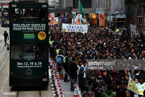 Pro democracy protesters walk past a tram during a New Year's day rally in Hong Kong on January 1 2013 Tens of thousands of protesters took to the...