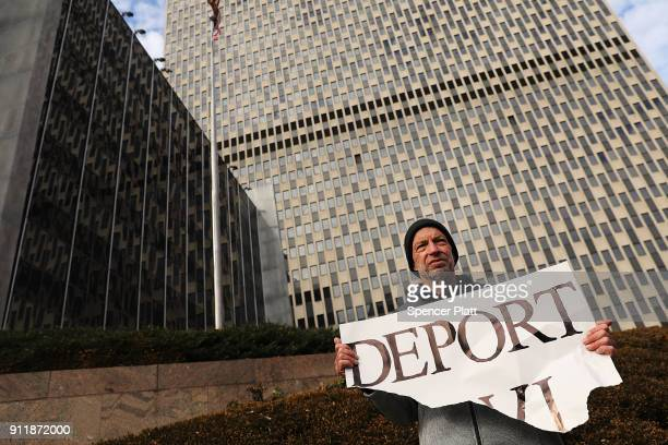 A pro Donald Trump protester holds up a sign calling for deportation as dozens of immigration activists clergy members and others participate in a...