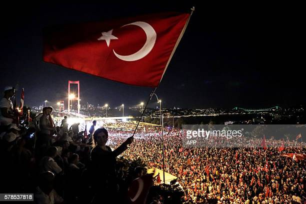 TOPSHOT Pro Erdogan supporters wave a Turkish national flag during a rally at Bosphorus bridge in Istanbul on July 21 2016 Thousands of Turkish...