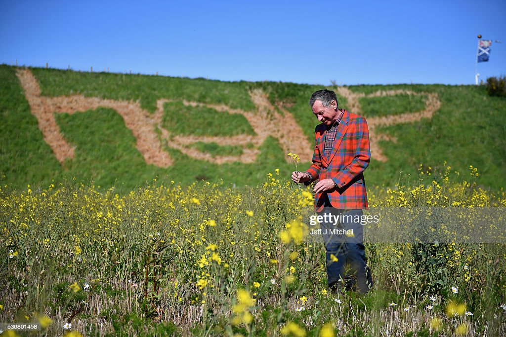 Pro EU supporter Fred Powada stands next to a help sign he made in the grass with weed killer on June 1, 2016 in Laurenckirk, Scotland. The United Kingdom will hold a referendum on June 23, 2016 to decide whether or not to remain a member of the European Union (EU), an economic and political partnership involving 28 European countries which allows members to trade together in a single market and free movement across its borders for citizens.