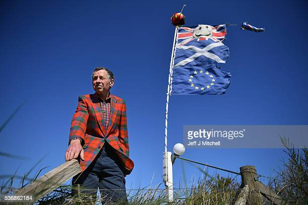 Pro EU supporter Fred Powada stands next tohie EU Saltire and Smiley Union Jack flags on June 1 2016 in Laurenckirk Scotland The United Kingdom will...
