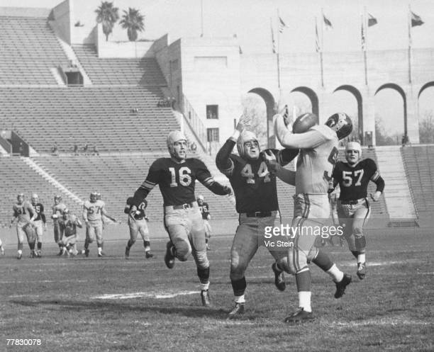 Pro Football Hall of Fame and Los Angeles Rams wide reciever Tom Fears catches a pass over Pittsburgh Steelers defenders Tony Campagno Gonzales...