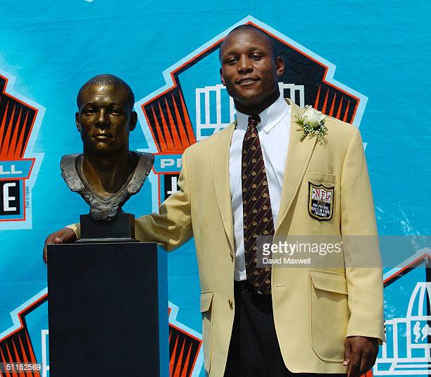 Pro Football Hall of Fame enshrinee Barry Sanders stands with his bust during the 2004 NFL Hall of Fame enshrinement ceremony August 8 2004 in Canton...