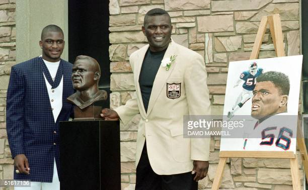 Pro Football Hall of Fame enshrinee Lawrence Taylor poses with his his bronze bust at the Hall of Fame Induction ceremony along with his son and...