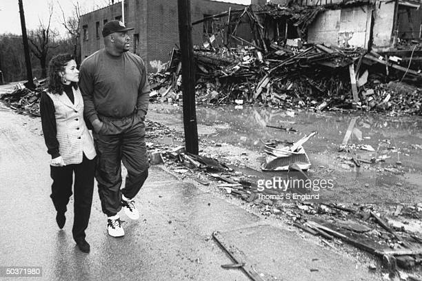 Pro football player Reggie White wife Sara walking past burnt rubble of Inner City Church where he acts as asst pastor