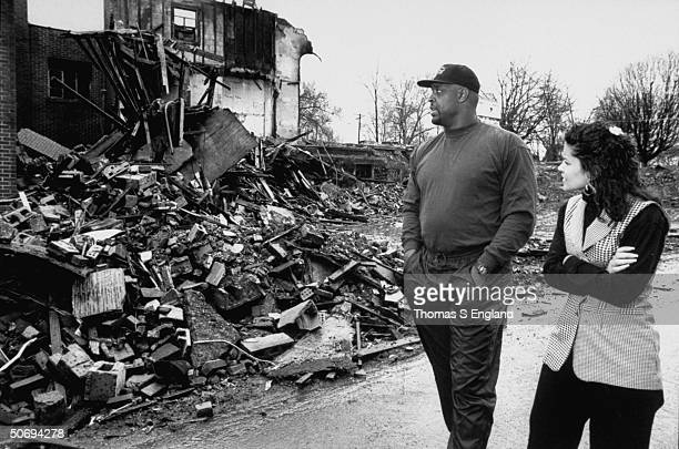 Pro football player Reggie White wife Sara walking past burnt rubble of Inner City Church where he acts as asst pastor re growing epidemic of arson...