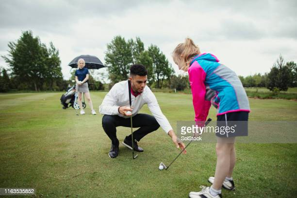 pro golfer aids younger girl golfer - teaching stock pictures, royalty-free photos & images