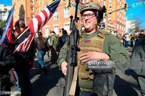 A pro gun supporter from Buffalo New York carries a high caliber sniper rifle during a gun rights rally outside the Virginia State Capitol grounds in...