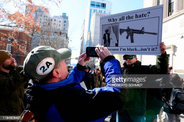 A pro gun supporter takes a photograph of a man holding a sign outside the Virginia State Capitol grounds in Richmond Virginia on January 20 2020...