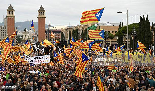 Pro independence demonstrators hold flags during a demonstration organized by ANC AMI and Omnium Cultural against Spains use of the courts to stop...