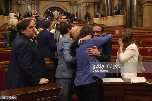 Pro independence members of Parliament embrace each other as they celebrate after the news that the Catalan Parliament voted in favour of...