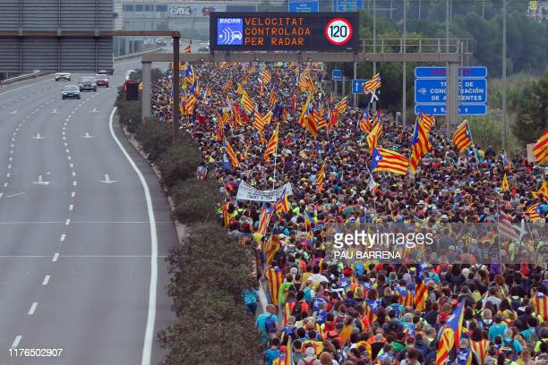 Pro independence protesters march along a highway in San Vicenc dels Horts, on October 18 on the day that separatists have called a general strike...