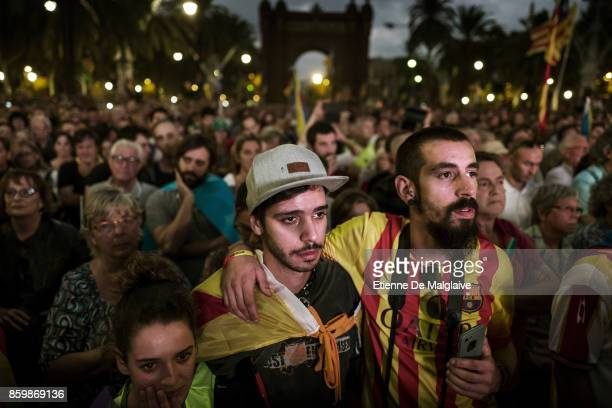 << Pro independence supporters react as they hear Catalan President Carles Puigdemont announce he will abide by the independence vote as they watch...