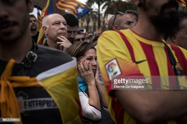 Pro independence supporters react as they hear Catalan President Carles Puigdemont announce he will abide by the independence vote as they watch on...