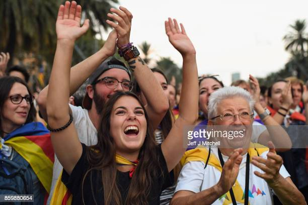 Pro independence supporters react as they watch on broadcast screens outside the Parliament of Catalunya as the Catalan President Carles Puigdemont...