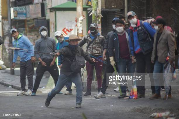 A pro Morales demonstrator uses a throwing weapon during a protest on November 15 2019 in La Paz Bolivia Morales flew to Mexico alleging a coup under...