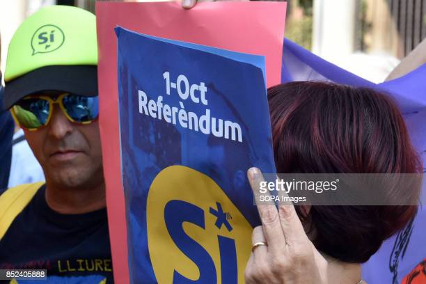 Pro referendum supporters are seen holding placards during a protest a week before the final vote for the independence of Catalonia A group of...