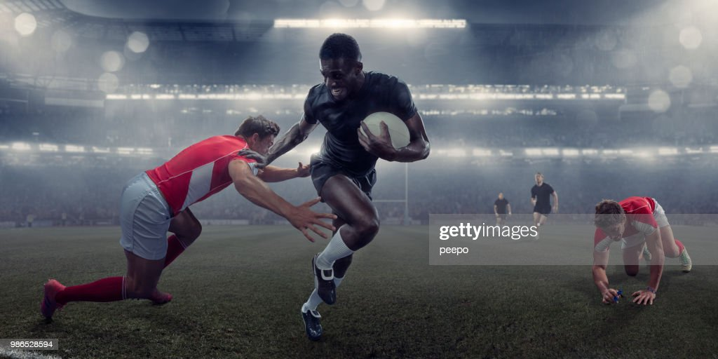 Pro Rugby Player Running With Ball Past Tackling Opponent : Stock Photo