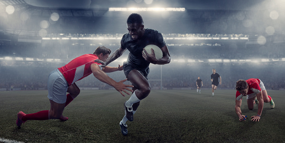 Pro Rugby Player Running With Ball Past Tackling Opponent 986528594
