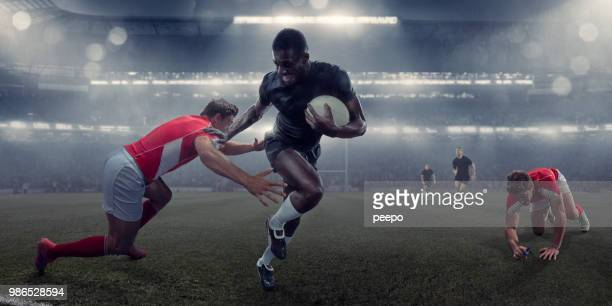 pro rugby player running with ball past tackling opponent - rugby stock pictures, royalty-free photos & images