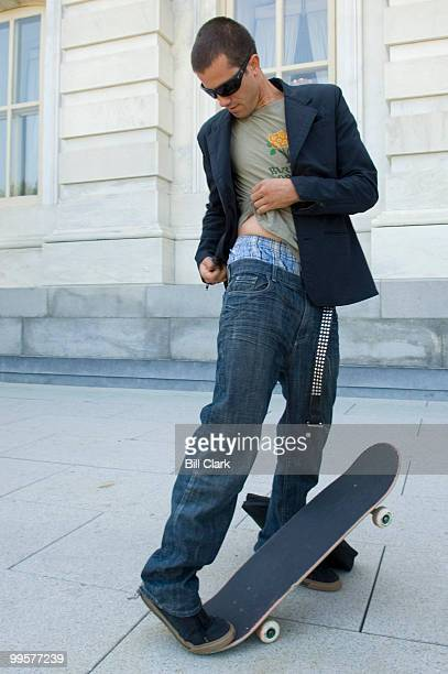 Pro skateboarder Bob Burnquist puts his metal studded belt back on after passing through security entering the Senate side of the Capitol on Thursday...