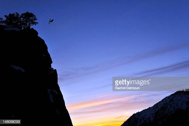 Pro skier Josh Daiek performs a front flip at sunset while ski BASE jumping off of Lovers Leap in Strawberry, CA.