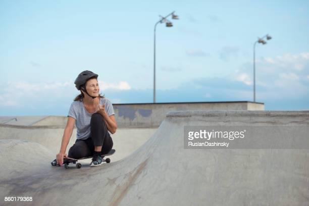 Pro sportliche senior Frau skateboarding.