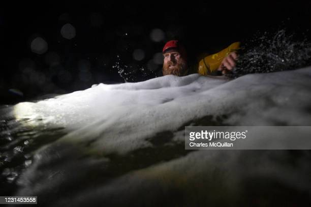Pro surfer Al Mennie swims through heavy surf at Downhill strand as he completes his 100KM night swim for charity on March 1, 2021 in Portrush,...