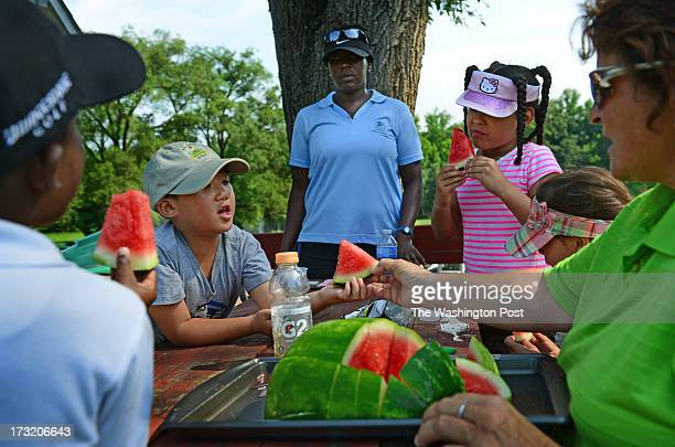 Pro Troy Beck hands out watermelon to junior golfers Xavier Adams, David Zhang, instructor Dana Coleman, Lauren Foster and Katy Asher during a break...