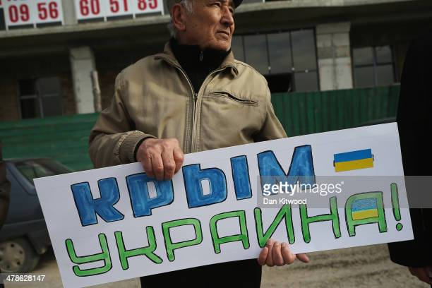 Pro Ukrainian man against the forthcoming referendum in Crimea holds a sign that reads 'Crimea Ukraine' as protesters gather along the road on March...