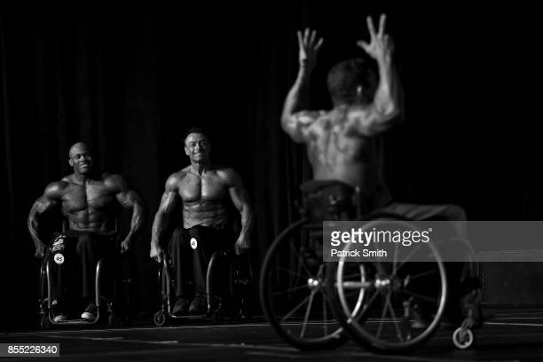 Pro Wheelchair Bodybuilder Johnny Quinn performs his single routine as competitors in his division Harold Kelley and Steven Lister smile during...