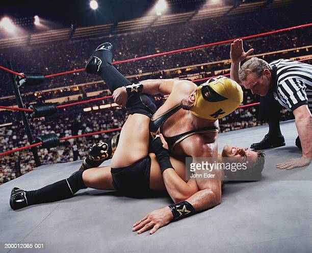 pro wrestler pinning opponent on mat, referee counting down - wrestling stock pictures, royalty-free photos & images