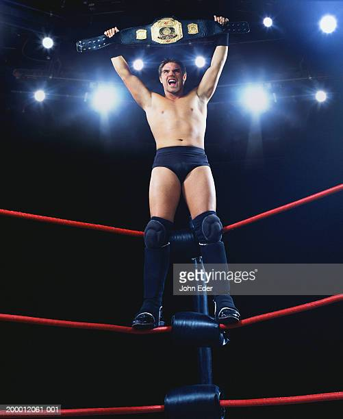 pro wrestler standing on ropes, holding championship belt - belt stock pictures, royalty-free photos & images