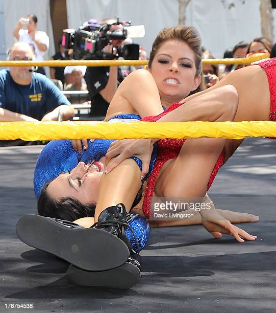Pro wrestler/journalist Maria Menounos and WWE Diva Brie Bella wrestle at the WWE and E's Total Divas takeover of SummerSlam at Nokia Plaza LA LIVE...