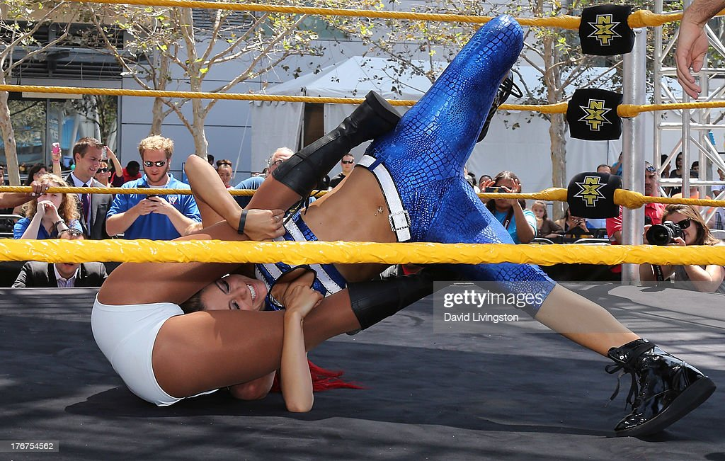 Pro wrestler/journalist Maria Menounos (in blue) and WWE Diva Eva Marie wrestle at the WWE and E!'s Total Divas take-over of SummerSlam at Nokia Plaza L.A. LIVE on August 18, 2013 in Los Angeles, California.