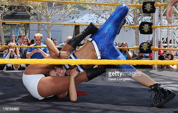 Pro wrestler/journalist Maria Menounos and WWE Diva Eva Marie wrestle at the WWE and E's Total Divas takeover of SummerSlam at Nokia Plaza LA LIVE on...