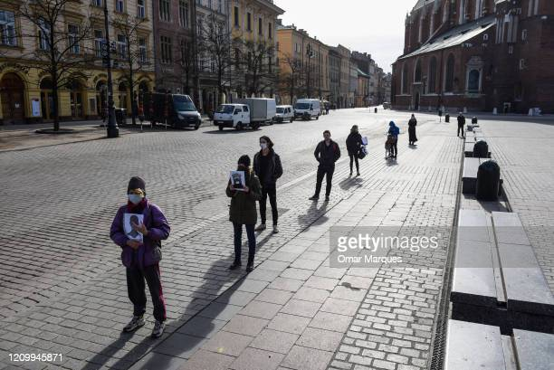 Proabortion activists wear protective masks and hold banners as they take part in a protest in front of a Biedronka supermarket at Krakow's Unesco...
