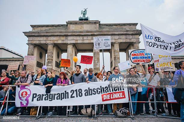 Proabortion protesters stand behind a banner that reads 'Abolish article 218' in front of Brandenburg Gate during their counterdemonstration against...