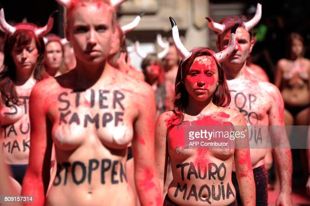 Proanimal rights activists stand after spreading red powder on themselves and breaking fake 'banderillas' to protest against bullfighting and...