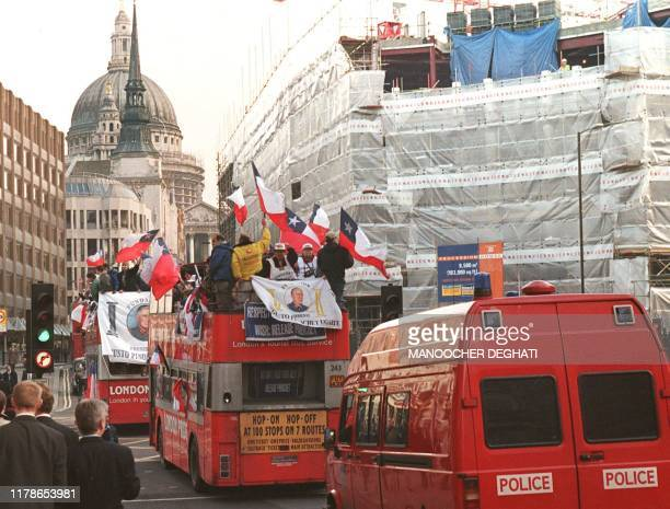 ProAugusto Pinochet protestors ride on an open top bus followed by a police van through the streets of London 10 December a day after British Home...